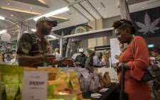 A vendor at the Cannabis Expo at Time Square in Menlyn explains products to a customer. Picture: Thomas Holder/EWN