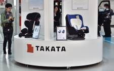 This file photo taken on 11 November, 2014 shows visitors looking at displays of Japanese auto parts maker Takata Corp at a car showroom in Tokyo. Picture: AFP.