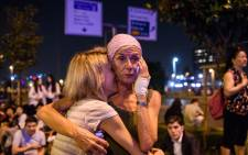 Passengers embrace outside Ataturk airport`s main entrance in Istanbul on 28 June 2016. Picture: Ozan Kose/AFP.