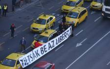 Hungarian taxi drivers hold a hold a sign reading 'Ban Uber' in downtown Budapest on 18 January 2016 during a taxi drivers' demonstration against Uber application. Picture: AFP.