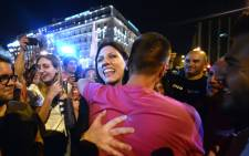 Greek Parliament's president and Syriza party member, Zoe Kostantopoulou (C) embraces a 'No' supporter , as she joins the celebrations in front of the parliament latein Athens on 5 July, 2015. Picture: AFP.