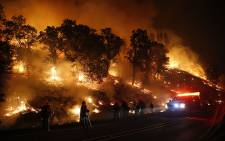 Firefighters with the Marin County Fire Department's Tamalpais Fire Crew monitor a backfire as they battle the Valley Fire on 13 September, 2015 near Middletown, California. Picture: AFP