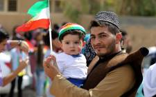 An Iraqi Kurdish man poses as he carries a child wearing the Kurdish flag on his head during a celebration in the northern city of Kirkuk on 25 September, 2017 as Iraqi Kurds vote in a referendum on independence. Picture: AFP.