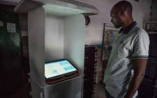 An agent of the National Independent Electoral Commission (CENI) tests a voting machine that arrived at the polling station in Lubumbashi, on the eve of the presidential, legislative and provincial elections on 29 December 2018. Picture: AFP