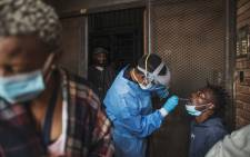 A Gauteng Health Department official collects samples from a man during a door-to-door COVID-19 coronavirus testing drive in Yeoville, Johannesburg, on 3 April 2020. Picture: AFP