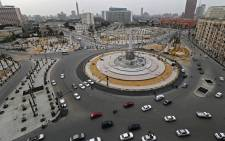Cars drive in the Egyptian capital Cairo's Tahrir square, shortly before the first day of a two-weeks night-time curfew imposed by the authorities to contain the spread of the novel coronavirus began on 25 March 2020. Picture: AFP
