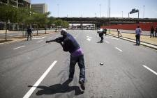 A refugee hurls a rock at police on Heerengracht Street in Cape Town during a riot. Picture: Thomas Holder/EWN