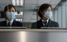 Taiwan's Centre for Disease Control staff stand at the entrance of Sungshan Airport in Taipei on April 4, 2013. Taiwan enhanced its level of alert against bird flu and set up a contingency centre after China's report of seven people infected with a new strain of avian influenza, including two deaths. Picture: AFP