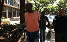 FILE: Crime Intelligence operative Morris Tshabalala (in orange) arrives at the Pretoria Commercial Crimes Court on 19 January 2018. Picture: Barry Bateman/EWN