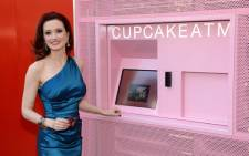 Model and television personality Holly Madison poses at a cupcake ATM at the grand opening of Sprinkles Cupcakes at The LINQ on 21 March 2014 in Las Vegas, Nevada. Picture: AFP.