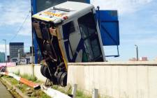 A Metrobus hangs over a bridge after the driver apparently lost control of the vehicle and crashed through the barrier wall on 25 February 2015. Picture: Masego Rahlaga/EWN.