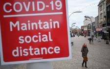 FILE: A woman wearing a face mask as a precaution against the transmission of the novel coronavirus walks by a sign encouraging social distancing in a street in Blackpool, Lancashire on 16 October 2020. Picture: AFP.