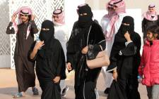 FILE: A picture taken on 19 January 2018 shows Saudi women and men walking during the King Abdulaziz Camel Festival in Ruma. Picture: AFP.