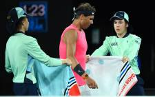 FILE: Ball boys give towels to Spain's Rafael Nadal during a break in his men's singles quarterfinal match against Austria's Dominic Thiem on day ten of the Australian Open tennis tournament in Melbourne on 29 January 2020. Picture: AFP.