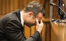 Oscar Pistorius while a witness recounts to the court the moments after the murder during the fourth day of his trial at the High Court in Pretoria on 6 March 2014. Picture: Pool.