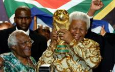 FILE: Nelson Mandela holding the Jules Rimet World cup beside Archbishop Desmond Tutu at the FIFA headquarters in Zurich. Picture: AFP.