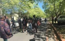 Stellenbosch University students walk behind a police van on campus grounds on 23 September 2016. Picture: Monique Mortlock/EWN.