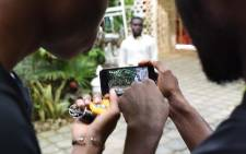 Two participants in a workshop film with their smart-phones on 30 March 2019 during the second edition of the Bushman Film Festival, the first Francophone film festival in West Africa focused on smartphone filming, in Abidjan. Picture:  AFP.