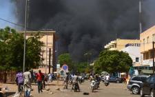 People watch as black smoke rises as the capital of Burkina Faso came under multiple attacks on 2 March 2018, targeting the French embassy, the French cultural centre and the country's military headquarters. Picture: AFP