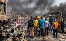 Medics and onlookers after a gas explosion destroyed buildings and killed at least 15 people, in Nigeria's commercial capital Lagos on 15 March 2020. Picture: AFP