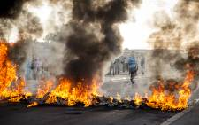 Residents navigate their way around burning tyres set alight by angry residents in Vrygrond. Angry taxi drivers are protesting against two few issued permits. Picture: Thomas Holder/EWN