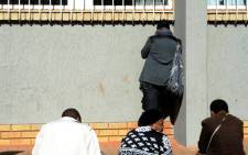 Suspect Lindray Khakhu's mother tries to avoid cameras while standing outside the Sophiatown Magistrates Court on Tuesday 5 August 2014 ahead of his appearance. Picture: Sapa.