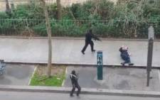 This screengrab from a video posted online shows armed men approaching a man who was shot moments before on a Paris street near the Charlie Hedbo offices on 7 January 2015. Seconds later the gun men shoots the victim a second time.