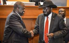 FILE: South Sudan's President Salva Kiir (R) and his former deputy turned rebel leader Riek Machar shake hands as they agree to a peace deal at the 33rd Extraordinary Summit of Intergovernmental Authority on Development (IGAD) in Addis Ababa, on 12 September 2018. Picture: AFP.