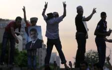 "Supporters of deposed president Mohamed Morsi (on the poster) flash the sign of victory atop a wall during a rally outside the headquarters of the Republican Guard in Cairo on 9 July 2013. Egypt's armed forces warned in a statement against any attempt to disrupt the country's ""difficult and complex"" transition. Picutre:AFP"