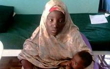 This handout picture taken in Damboa and released by the Nigerian army on 18 May, 2016 shows Amina Ali posing with her 4-month old baby Safiya, one of 219 girls abducted from their school in Chibok more than two years ago, after she was released by Nigerias army. Picture: AFP.