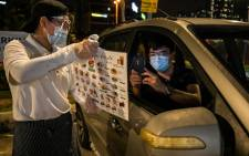 A waiter brings a menu for the dine-in car service to a customer outside the Padi House restaurant in Cyberjaya, outside Kuala Lumpur, Malaysia, on 9 February 2021. Picture: Mohd Rasfan / AFP