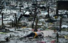 The body of a dead man is seen at the bay of Tacloban on 10 November 2013 amid the wreckage caused by Typhoon Haiyan in the Philippines. Picture: Noel Celis/AFP.