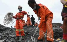 Red Cross workers pull on a cable attached to a rescue boat searching for bodies from the site of a landslide by jade mines near Hpakant in Kachin state on July 4, 2020. Picture: AFP.