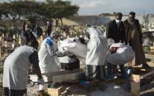 Members of a family dressed in personal protective equipment put the body of a man who died of COVID-19 into a grave during a Muslim burial at the Klip Road Cemetery in Grassy Park, Cape Town, on 9 June 2020. Picture: AFP.
