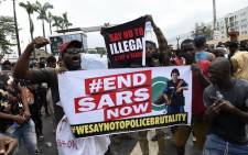 People carry placards in continuation of ongoing demonstrations to call for the scrapping of the controversial police unit at Ikeja, on October 9, 2020. Picture: AFP