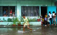 A young evacuee wades through flooded school grounds while others look on from a school building being used as an evacuation center in the city of Legaspi in Albay province, south of Manila on 14 December, 2015, as typhoon Melor approaches the city. Picture: AFP.