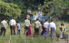 Myanmar authorities look at a group of Rohingya Muslim women walking on a field in Kyauktan township south of Yangon on 16 November 2018, after their boat washed ashore. Picture:  AFP