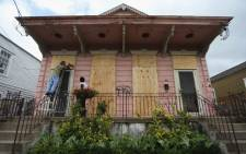 A couple board up their home before Hurricane Isaac, which still bears a marking from Hurricane Katrina, on August 28, 2012 in New Orleans, Louisiana. Picture: AFP.