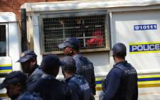 Mineworkers are transported under heavy police guard from the Ga-Rankuwa Magistrate's Court, north of Pretoria on Tuesday, 28 August 2012 where they appeared following the violence at Lonmin's Marikana mine. Picture: Sapa.