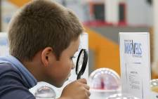 FILE: A school boy peers at the Miniature Marvels exhibit through a magnifying glass at the Cape Town Science Centre. Picture: Aletta Harrison/EWN.