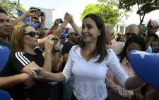 Opposition deputy Maria Corina Machado greets supporters during a protest in front of the OAS headquarters building in Caracas on 3 March 2014. Picture:  AFP.