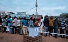 People wait in a line to vote at a polling station in Kampala, Uganda, on 14 January 2021. Picture: YASUYOSHI CHIBA/AFP
