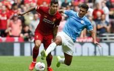 Liverpool midfielder Roberto Firmino (L) is challenged by Manchester City midfielder Rodrigo (R) during the English FA Community Shield football match between Manchester City and Liverpool at Wembley Stadium in north London on 4 August 2019. Picture: AFP