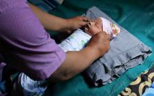 Abidah Asian Games, a newborn baby girl named as such after she was born hours before the games' opening ceremony, is tended to at the family home in Palembang on 21 August 2018. Picture: AFP.