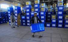 Afghan employees of the Independent Election Commission (IEC) carry ballot boxes at a warehouse in Herat province on 17 October, 2018. Picture: AFP.