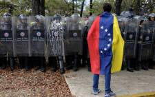 A Venezuelan student stands in front of riot police during a protest against the government of President Nicolas Maduro in Caracas on 12 March 2014. Picture: AFP.