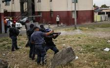 Police fire a stun grenade into a crowd gathered outside CT international airport. Picture: Anthony Molyneaux/EWN