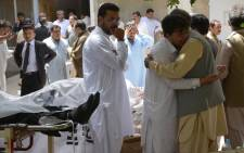 Pakistani relatives mourn next to bodies of victims after a bomb explosion at a government hospital premises in Quetta on 8 August, 2016. Picture: AFP.