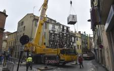A container is lifted over a building by a crane before being used by doctors of the French Urgent Medical Aid Service (SAMU) to evacuate a man suffering from morbid obesity from the first floor of his home in Perpignan, southwestern France, on 1 December 2020. Picture: AFP.