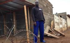 Lufuno Netsogane stands in front of his shack; a Citi Golf slammed into it on Good Friday killing a four year-old girl. Picture: Vumani Mkhize/EWN.